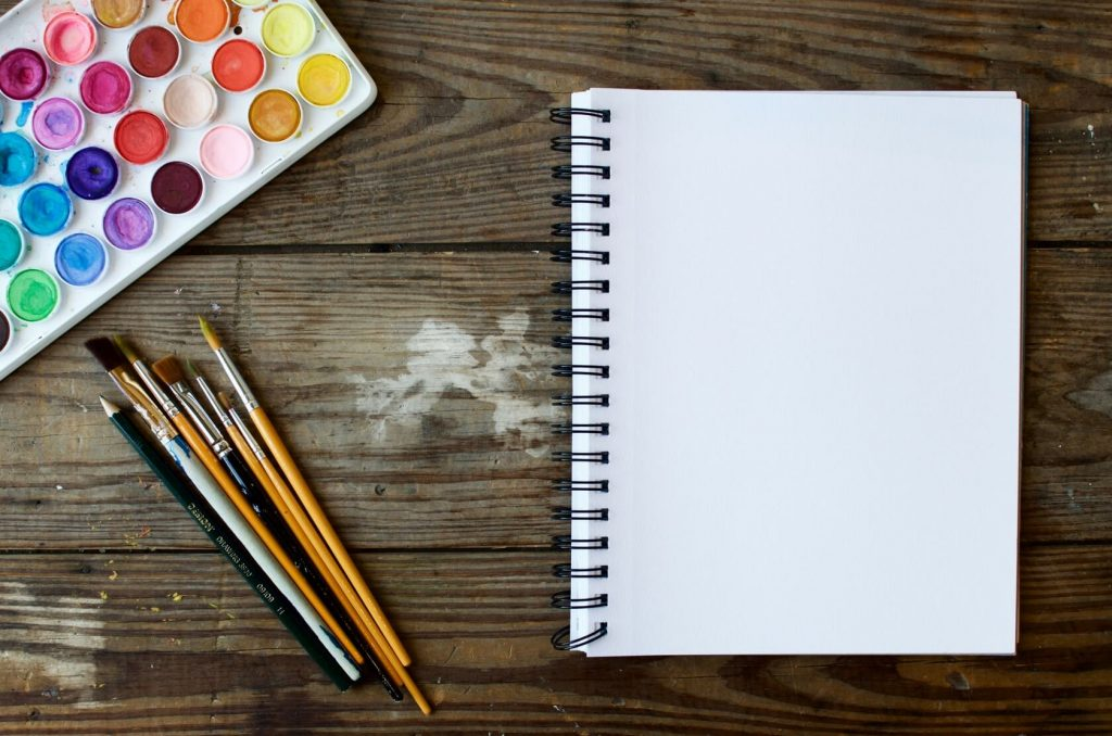 Notebook, paint brushes and painting colors to help you learn English visually.